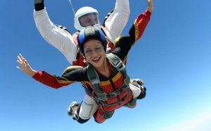 Two people jumpting with a parachute.