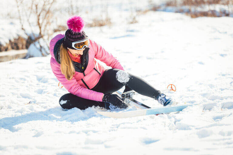 An injured woman sitting down on the snow