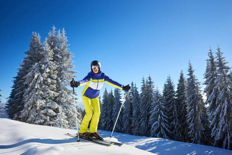 A happy woman skiing down a beginner slope