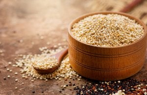 A bowl full of quinoa and a wooden spoon.