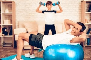 A dad and his son working out at home.