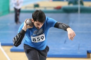 A male athlete about the launch a shot put.