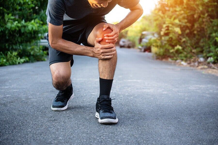 A male runner clutching his knee in pain.