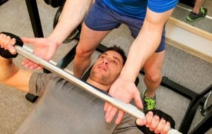 A man doing supervised bench presses.