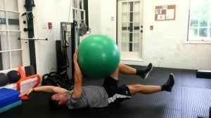 A man in a gym using an exercise ball.