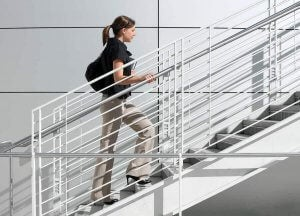 A woman climbing the stairs to improve circulation in her legs.