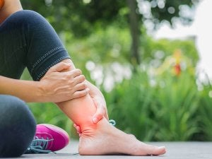 A woman holding her ankle because she has a sprain.