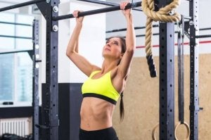 A woman learning to do pull-ups.