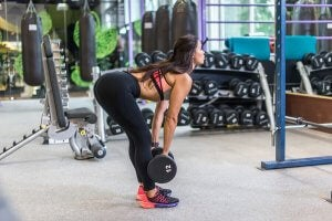 A woman performing a dumbell deadlift.