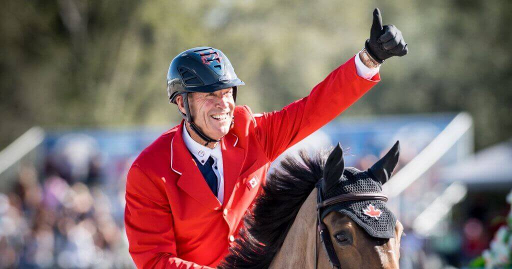 Ian Millar on a horse giving a thumbs-up.