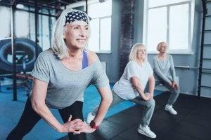 Three elderly women doing lunges.