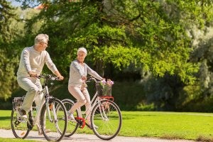 Two elderly people riding bikes outside.