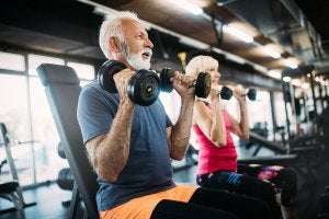 Two elderly people working out in a gym.