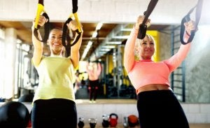 Women exercising at the gym with TRX bands.