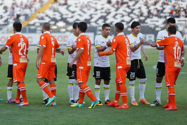 Members of the Colo-Colo and the Cobreola team greeting each other before disputing of the classic encounters of Chilean soccer