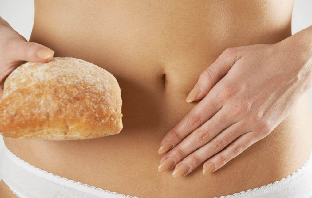 Woman holding a piece of bread next to her abdomen