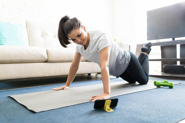 A woman using an exercise mat to work out at home