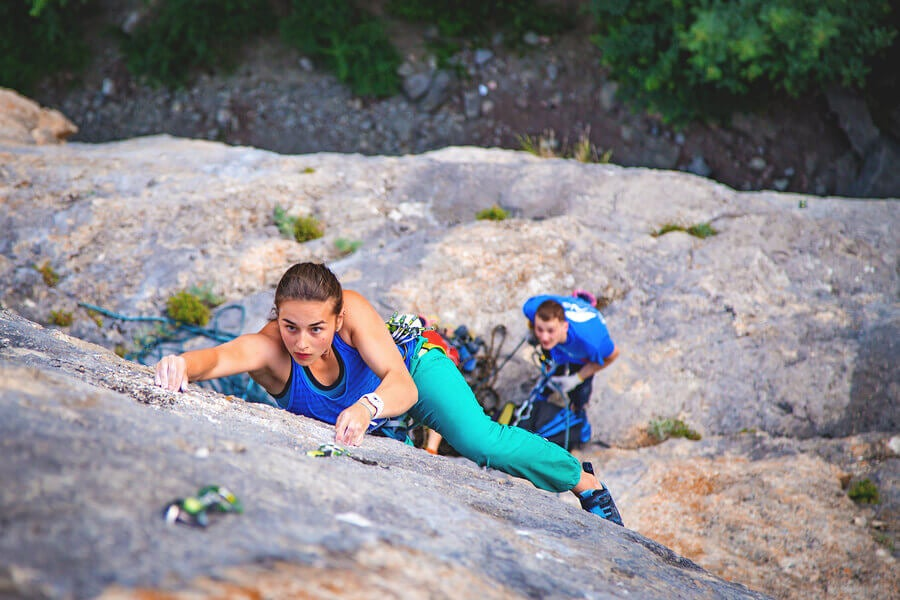 Two people doing mountain sports with the proper safety equipment