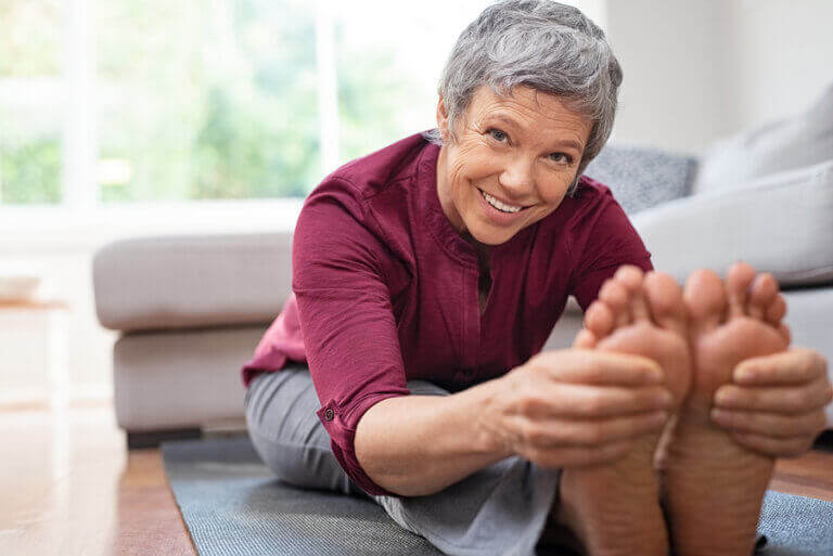 An older woman using exercise to reduce her feelings of stress during quarantine