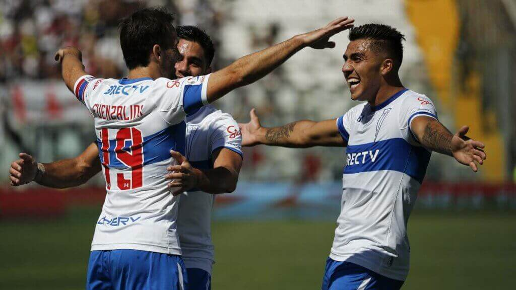 Three players from the Universidad Catolica team hugging after winning one of the classic encounters of Chilean soccer