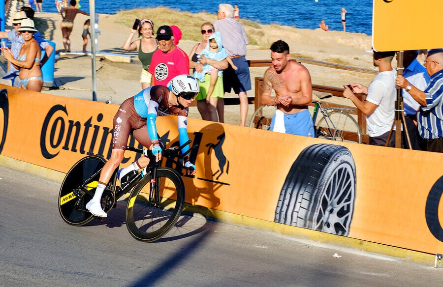 A rider during the Vuelta a España Grand Tour and several people cheering in the background