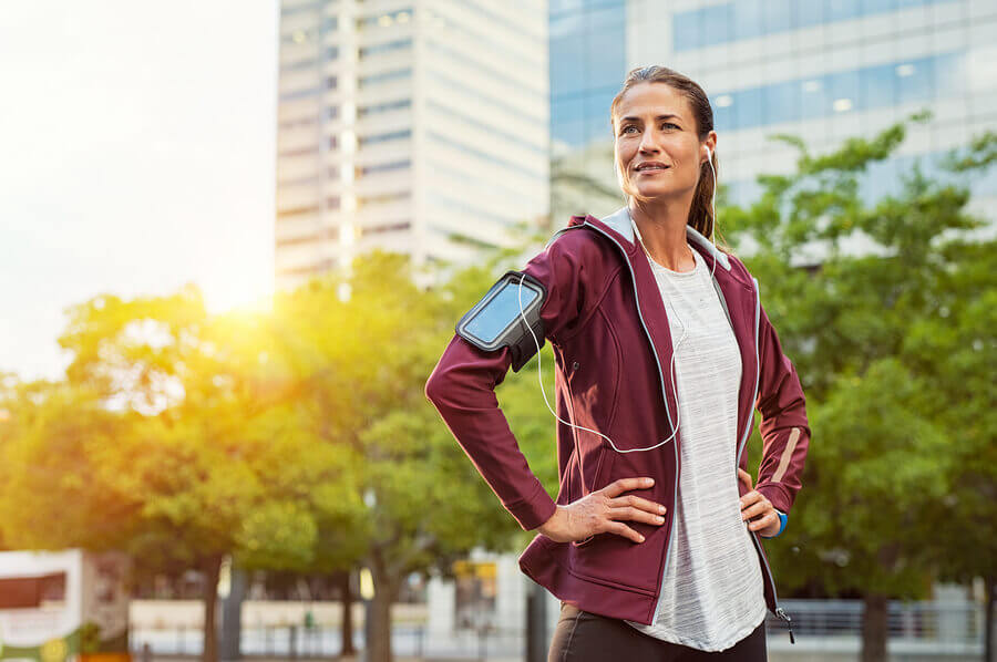 A woman running outside to boost the health benefits of her workout
