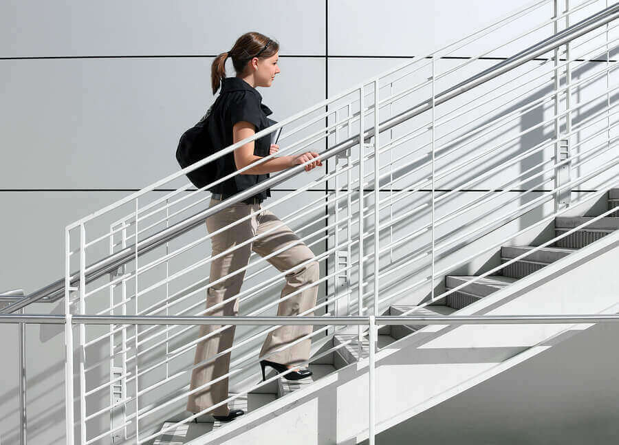 A woman using the stairs on her way to work to maintain muscle mass during quarantine