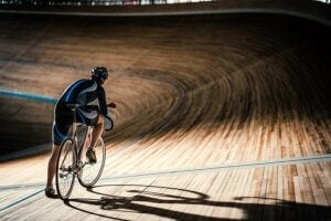 A lone cyclist on a dark velodrome.