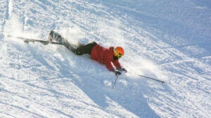 A person falling down a snowy hill.