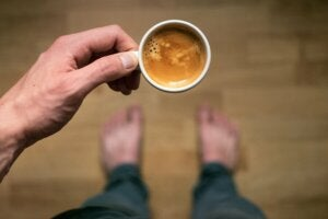 A person holding a cup of coffee.