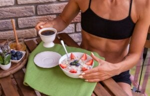 A woman eating oatmeal with coffee.