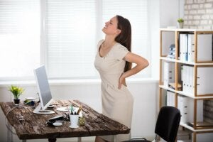 A woman suffering from lower back pain at work.