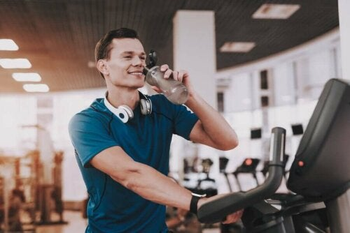 A guy drinking water at the gym to stay hydrated in the winter.