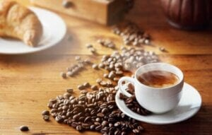 A cup of espresso surrounded by coffee beans.