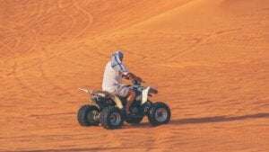 A man on a quadbike in the desert.