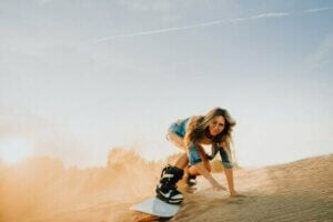 A woman sandboarding, which is just one of many desert adventure sports.