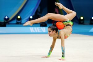 An individual rhythmic gymnast with a ball.