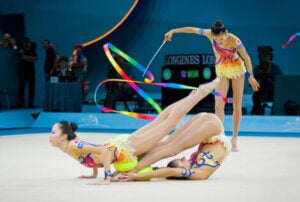 Three rhythmic gymnasts in the middle of a competition.