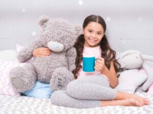 A girl on her bed drinking milk with her teddy.