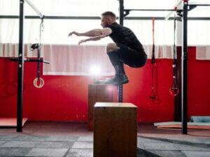 A man doing a box jump to strengthen his legs.