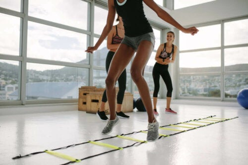 A woman training with an agility ladder.
