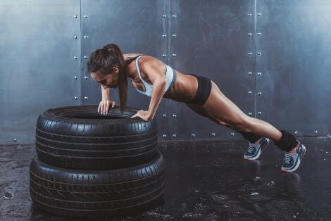 A woman doing CrossFit exercises with a tires