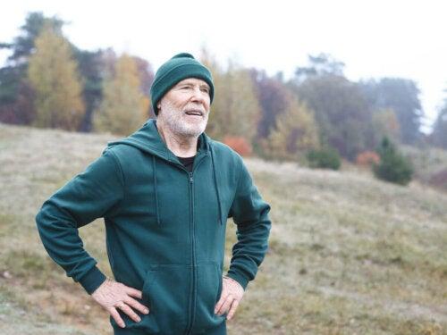 Older man running outside, stopping to breathe.