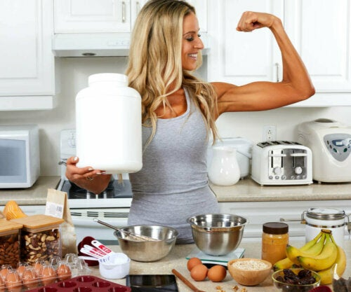 Woman in the kitchen, flexing while holding protein powder with protein rich foods on the counter.