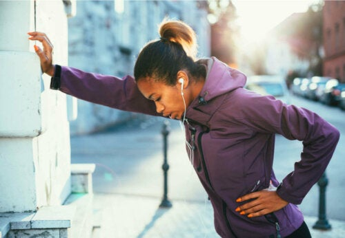 Woman leaning on a wall, tired from running.