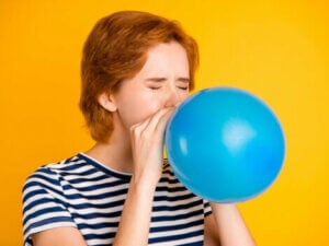 A teenager blowing up a balloon.