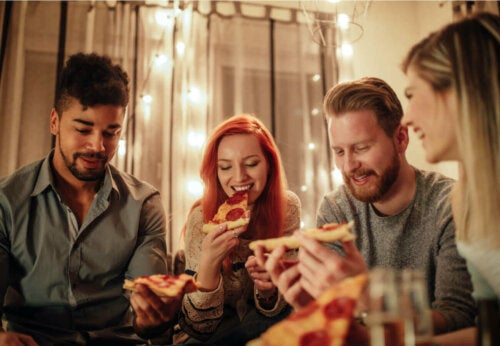 A group of friends eating pizza at dinner.