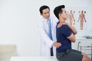 A male physiotherapist treating a male patient for trochanteric bursitis.