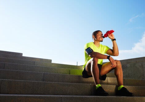 A runner drinking a sports drink to rehydrate
