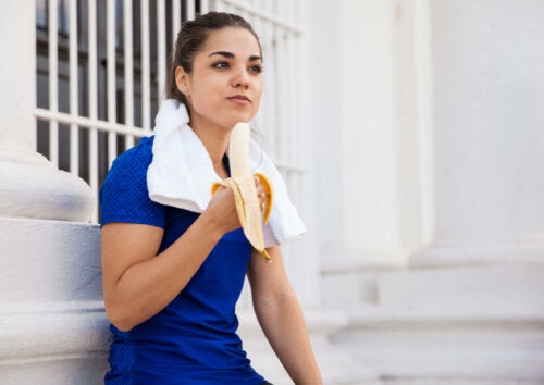 A woman eating fruit after exercising.